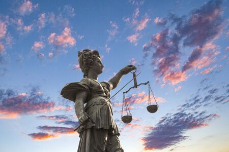 Statue of Lady Justice in front of the Romer in Frankfurt with dramatic sky Standard-Bild