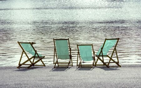 four empty deck chairs at the Hyde Park in London, UK