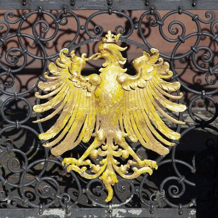 the golden eagle, heraldic animal and symbol for Frankfurt, at an old iron fence downtown at the Roemer. Stockfoto - 133479066