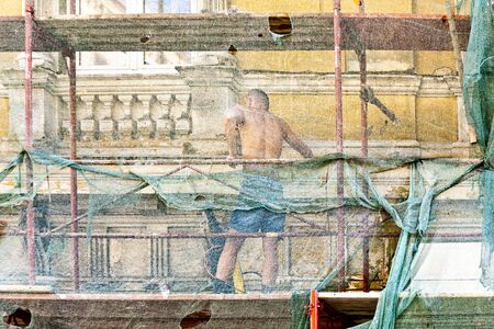 Vienna, Austria - November 21, 2009: man restores facade of buildings of the 19th century in Vienna, Austria. He is protected by a net.
