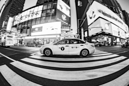 New York, USA - October 7, 2017: taxi driver with passengers crosses a pedestrian crossing at times square. Times square is a symbol for New York life and amusement. Editorial