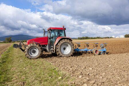 tractor is plowing the field in autumn Zdjęcie Seryjne