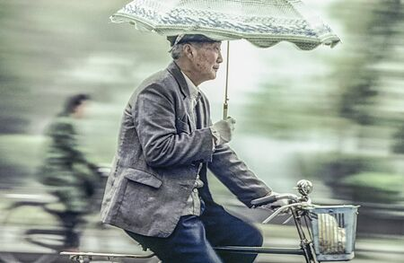 Beijing, China - August 1, 1982: old man rides his bicycle with umbrella in his arm. I 1982 bicycle was for more than 95 percent of chinese people the way for transportation even in Beijing.