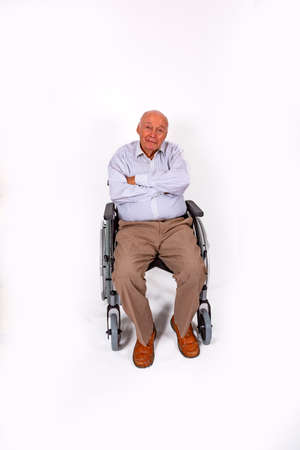 happy elderly man sits smiling in his wheelchair Stock Photo