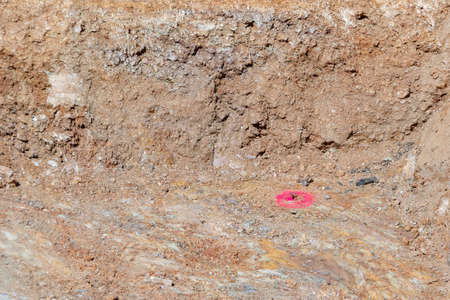 red marked measurement for a batter board in a hole of loam