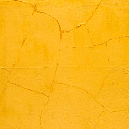 old cracked orange plaster wall in detail