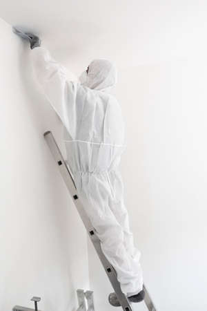 male painter in protective suit works on a ladder and straitens the wall with sandpaper
