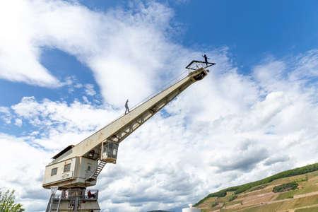 old crane still standing in Bingen at river Rhine with worker sculpture