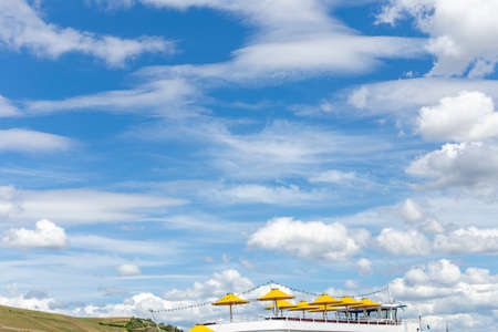 open yellow parasols at an cruise ship with spectacular blue and soft cloudy sky as symbol for touristic travel