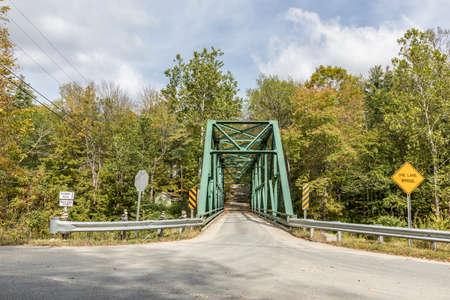small metal bridge spanning rock river in Williamsville, Vermont, USA