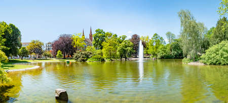 Summer landscape in the Kurperk (Spa Park) in Wiesbaden with bench and fountain, Germany