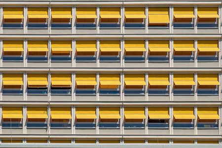 pattern of orange shutter sun protection at a facade of a modern building