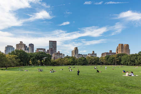 New York, USA - October 6, 2017: people relax in front of trees at Sheep Meadow Central Park in New York, USA.
