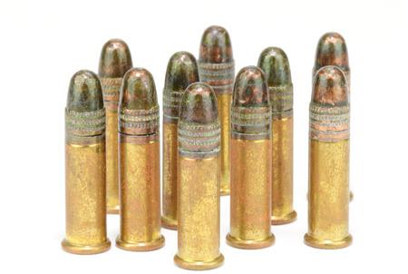 Ten, twenty-two   22  caliber rifle rounds, standing, on white Stock Photo