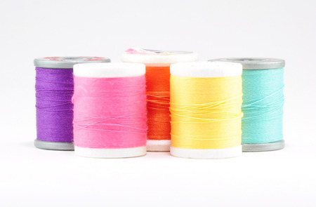 Five spools of sewing thread, arranged from left to right purple, pink, orange, yellow, light blue  Stock Photo