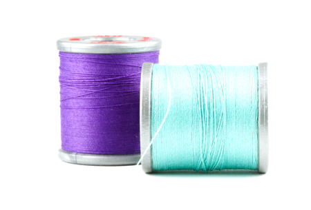 Two small spools of thread, on white