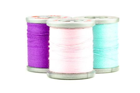 Three small spools of thread, on white