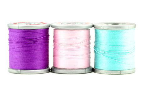 One each spool of purple, pink, and blue thread