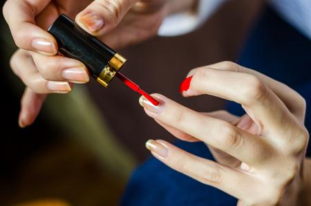 Frau mit langen Fingern, die ihre langen Nägel mit rotem Nagellack bemalt Standard-Bild