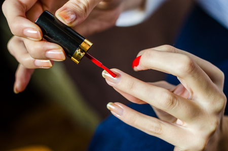 Woman with long fingers painting her long nails with red nail enamel Archivio Fotografico