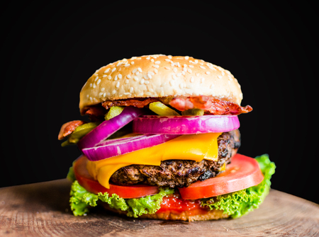 Burger on a wooden table against black background