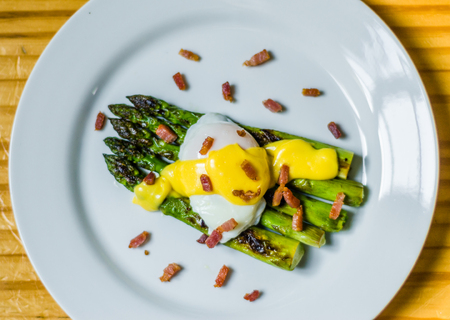 Close up photo of a poached egg with Hollandaise sauce, asparagus, and bacon 写真素材
