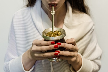 Young woman drinking traditional yerba mate tea