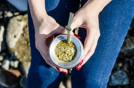 Junge Frau trinkt traditionellen argentinischen Yerba Mate-Tee aus Kalebassenkürbis Standard-Bild