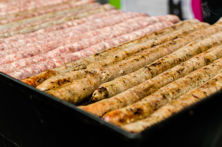 Argentina barbecue asado chorizo sausages and meat cooking on parilla grill