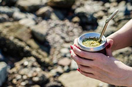 Young woman drinking traditional Argentinian yerba mate tea from calabash gourd Stock Photo