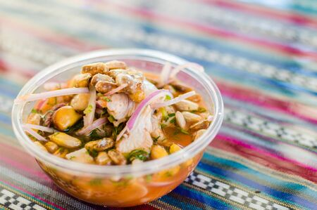 Peruvian mixed ceviche with red onion and fried corn at a street food market