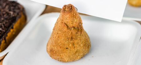 Traditional Brazilian coxinha chicken nugget at a street food market Standard-Bild - 124553720