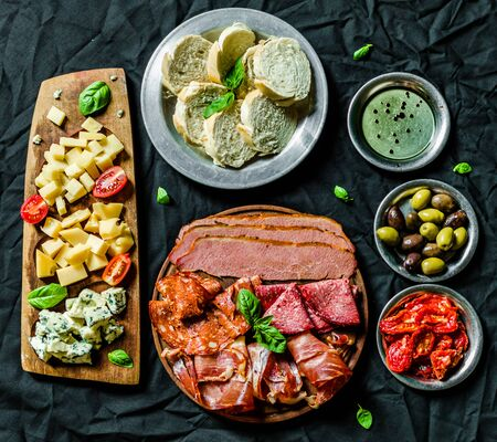 Italian cold meat and cheese antipasti delicatessen platter on black background