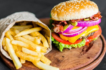 Burger and french fries on a wooden table against black background