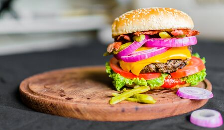 Burger on a wooden table against black background Stok Fotoğraf
