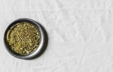 Yerba mate tea on a metal plate against white background
