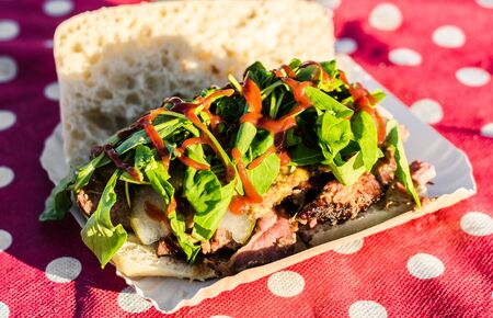 Sandwich with slow cooked smoked beef and bbq sauce at a street food market