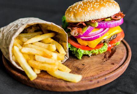 Hamburger en frietjes op een houten tafel tegen zwarte achtergrond