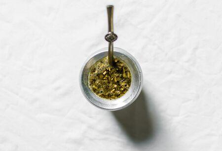 Yerba Mate-Tee in einem Kalebassenkürbis vor weißem Hintergrund. Selektiver Fokus