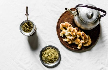 Yerba mate tea, croissants on a wooden board, and kettle on white background