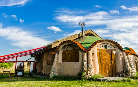Cute colorful cartoon fairytale house against blue sky and clouds on a sunny day Archivio Fotografico - 125687081