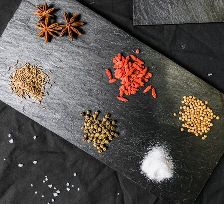 Large selection of different colorful contrast spices and seeds on slate