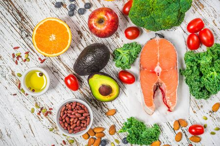 Selection of fresh fruit and vegetables, salmon, beans, and nuts