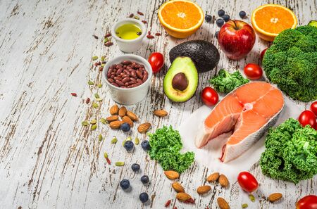 Selection of fresh fruit and vegetables, salmon, beans, and nuts.