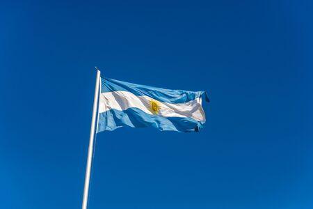 Argentina flag waving against blue sky on a sunny day.