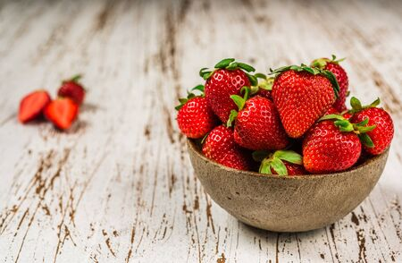 Bowl with fresh colorful organic strawberries fruit against wooden background