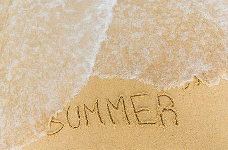Ocean sea waves running over the caption summer written on the sand.