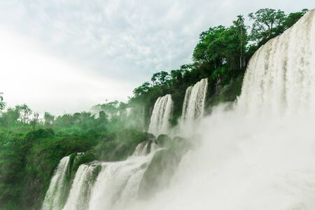 Wide angle landscape view of Iguazu falls waterfalls on a sunny day in summer.