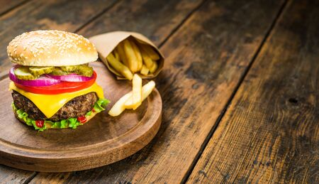 Cheese burger and french fries against wooden background. Tasty fast food.