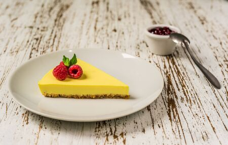 Lemon cheesecake with raspberries, mint, and jam against white wood background. Stock fotó
